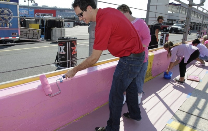 Joey Logano along with breast cancer survivors paint pit wall pink at Charlotte Motor Speedway